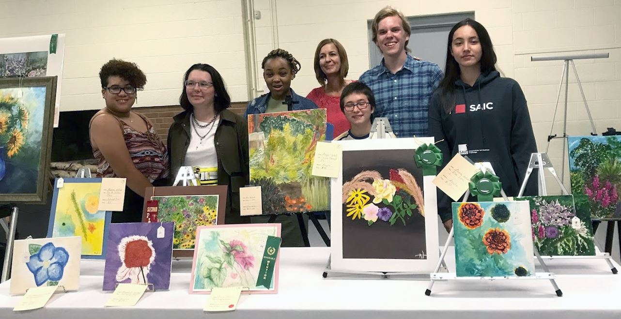 PleinAir 2019 student artists group photo with paintings on table